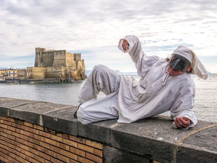 Portrait of man wearing mask lying on retaining wall against sea