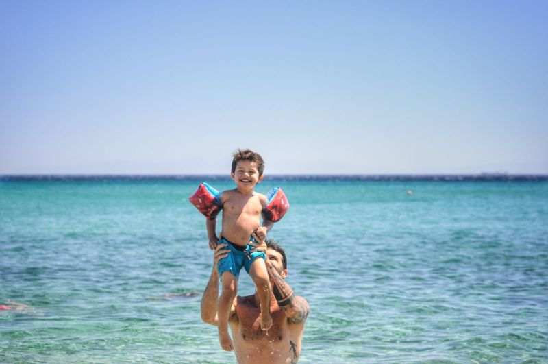 Shirtless father carrying happy son in sea against clear sky