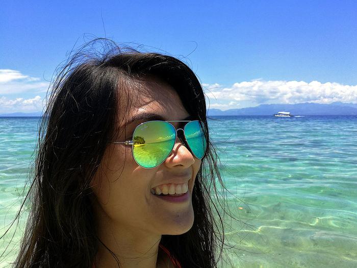 Woman wearing sunglasses in sea against sky