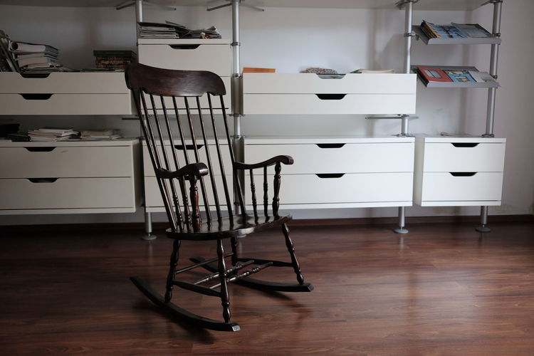 Rocking chair on hardwood floor against shelves at home