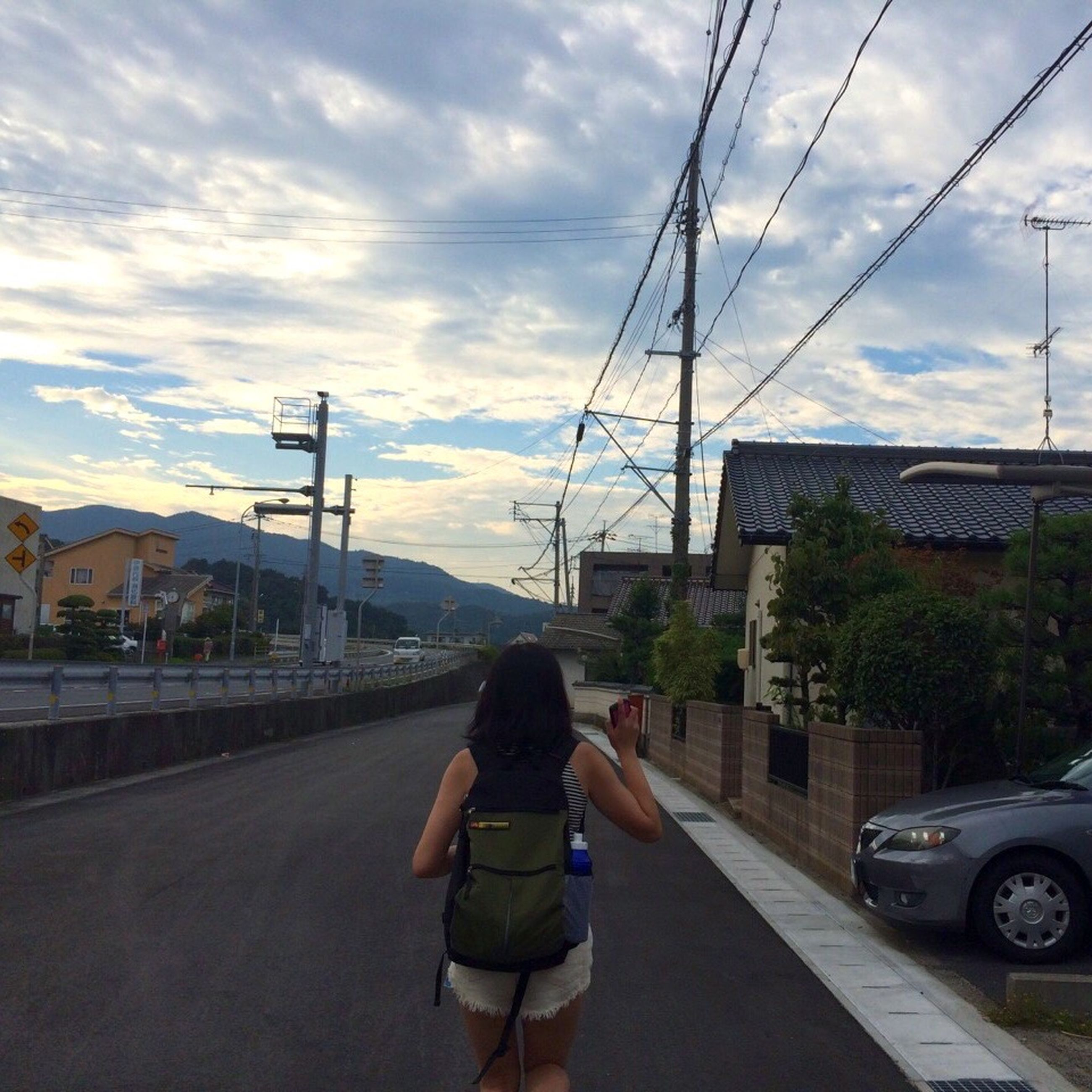 transportation, rear view, road, full length, street, sky, walking, mode of transport, on the move, architecture, person, car, land vehicle, cloud, casual clothing, riding, day, the way forward, mountain, cable, cloud - sky, power line, city life, outdoors