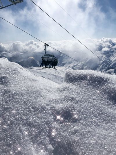 Overhead cable car on snow covered land against mountains and sky
