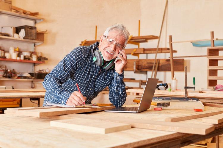 Portrait of senior man talking over mobile phone in workshop