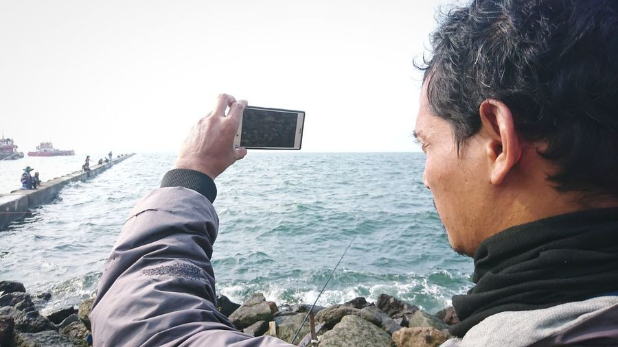 Midsection of man photographing sea