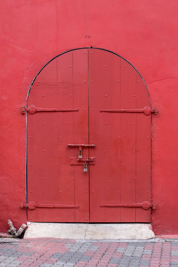 Old style Arched top wooden door painted in dark red set in red wall. Arch Archway Barrel Locks Building Door Doorway Exterior Wall Hinges Historic Locked Locks Old Style P9 Padlocks Paint Painted Red Secure Wood Wooden Entrance Closed Safety Architecture Security No People Built Structure Protection Day Building Exterior Wood - Material Metal Outdoors Pink Color Wall - Building Feature Lock Wall