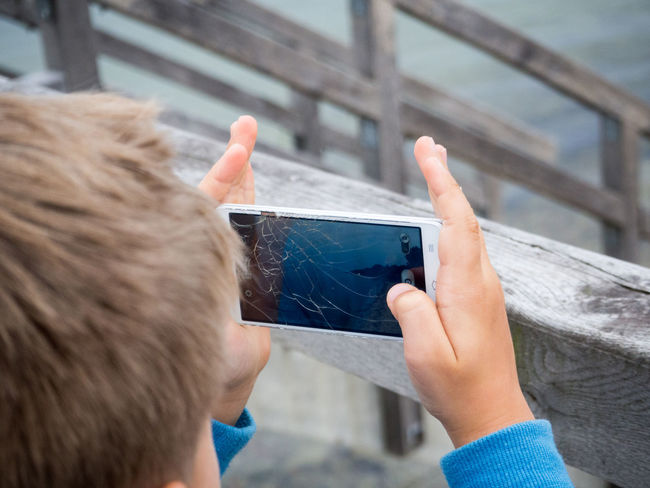 Broken Broken Screen Cellphone Clicking Communication Connection Device Screen Focus On Foreground Holding Leisure Activity Memories Mobile Phone Outdoors People And Places Person Photo Messaging Photographing Photography Themes Portability Portable Information Device Smart Phone Technology Using Phone Wireless Technology