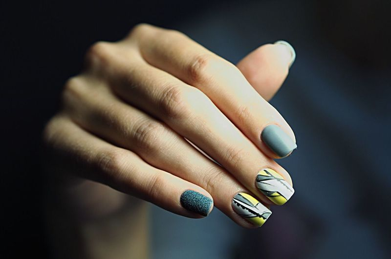 Cropped hand of woman with painted fingernails