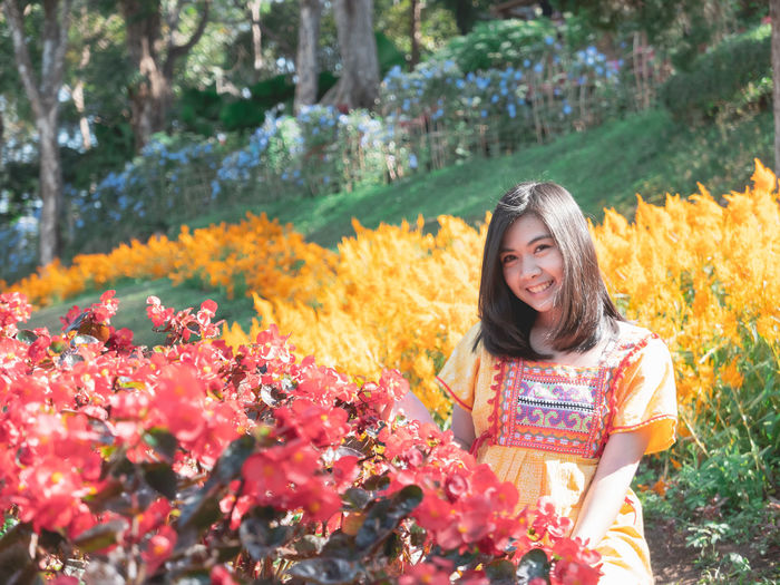 Portrait of smiling young woman standing amidst flowering plants