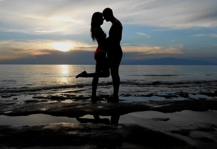 Silhouette Romantic Couple Embracing On Beach Against Sky During Sunset