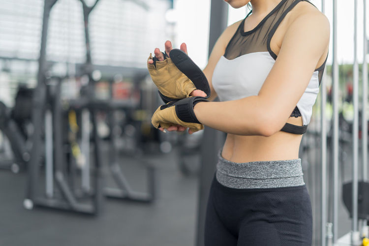 Midsection Of Young Woman Wearing Gloves At Gym