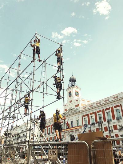 Low angle view of people working on building against sky