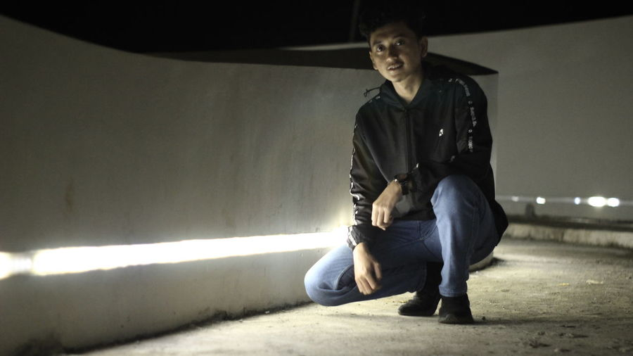 Portrait of young man sitting on wall at night