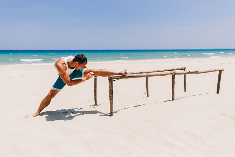 Man training and workout on beach. Fitness outdoors. Beach One Person Sand Sea Ocean Fitness Fitness Training Outdoors Man Males  Strong Yoga Stretching Workout Sport Leisure Activity Lifestyles Relaxing Exercising Water Beauty In Nature Real People