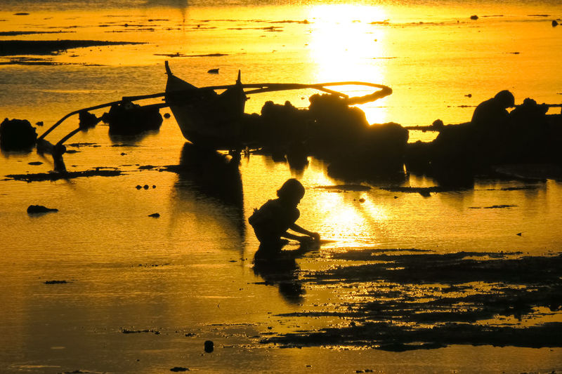 Child and fishing boat silhouette on an island beach in the Philippines Anda Anda Beach Beach Scene  Beach Sunset Beach Sunsets Boat Silhouette Bohol Child Playing Fishing Boat Silhouette Fishing Boats Fishing Village Island Life Island Living Island Scene Island Sunset It's More Fun In The Philippines Kid Playing Orange Sky Sunset Orange Sunset Playing In The Water Simple Life Sunset Scene Sunset Silhouette Village Lifestyle Village Photography