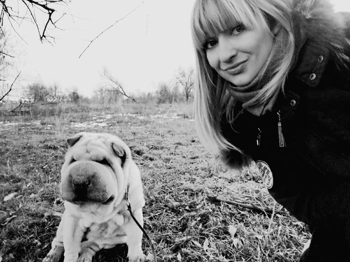 Portrait of smiling woman with dog sitting on grassy field