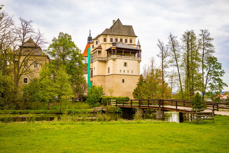 Medieval Blatna Castle in Czech Republic during spring season in Czech republic Castle Europe Old Architecture History Landmark Sky Travel Blatna Czech Historic Landscape Pond Tourism View Building Medieval Water Bridge Republic Tower Palace Beautiful Château Lake Nature Reflection Scenery Season  Blue Bohemia Historical Tree Clouds Czech Republic Forest Gothic Stone Outside Autumn Baroque Culture Czechia Exterior Outdoor City Construction Fantasy King Fort