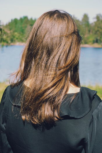 young woman looking at lake Black Dress Lake Back EyeEm Selects Water Young Women Headshot Women Lake Long Hair Rear View Close-up Sky Casual Clothing Tangled Hair Human Hair Head And Shoulders Tousled Hair Pensive Thinking Caucasian Pretty Hair Care Hairy  Body Adornment Wearing Shore