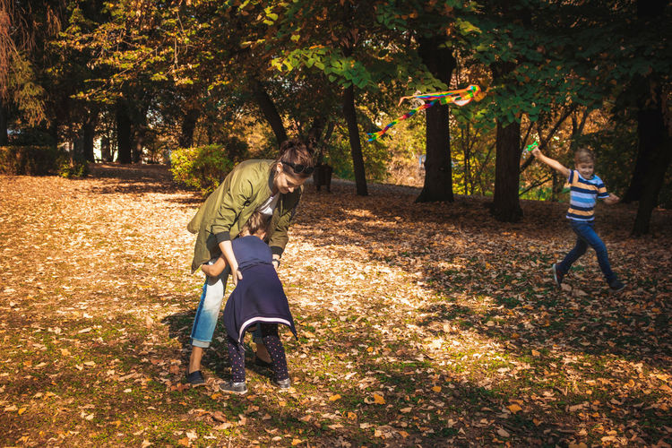 Woman playing with daughter by son running with kite in park during autumn