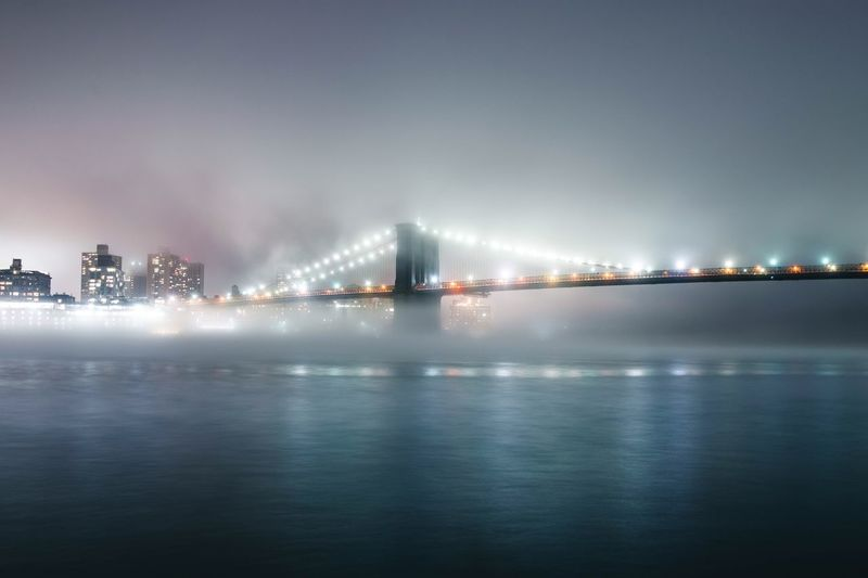 Illuminated brooklyn bridge over river at night