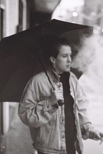 A girl smokes a cigerette in the rain Lifestyles Waist Up One Person Real People Indoors  Leisure Activity Day Warm Clothing Portrait Young Adult People Cigerette Rain Umbrella NYC Streetphotography Street Photography Brooklyn