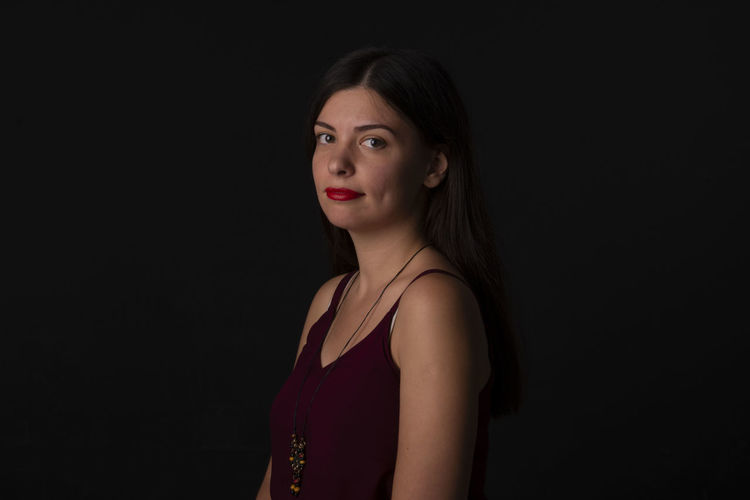 Portrait Of Smiling Young Woman Against Black Background