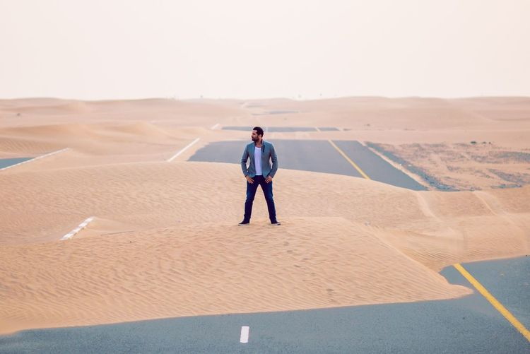 Full length of handsome young man standing on sand at desert against clear sky