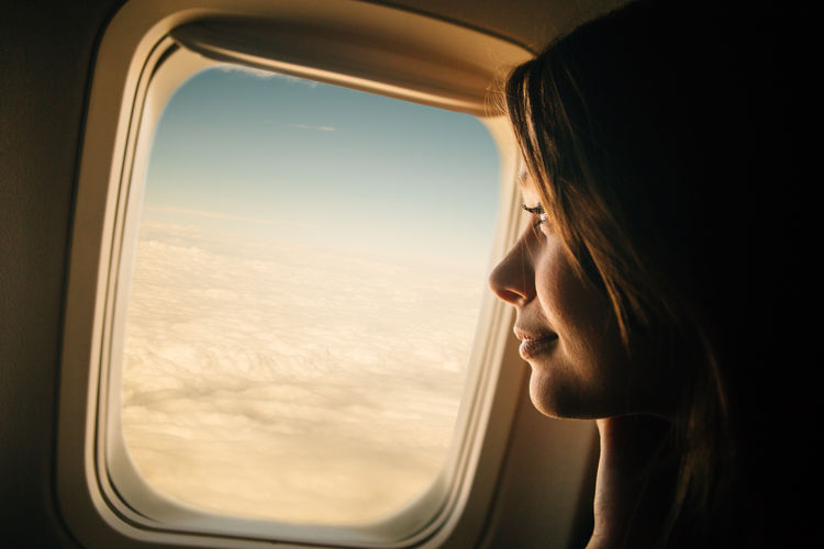 Close-up of mid adult woman looking through window in airplane