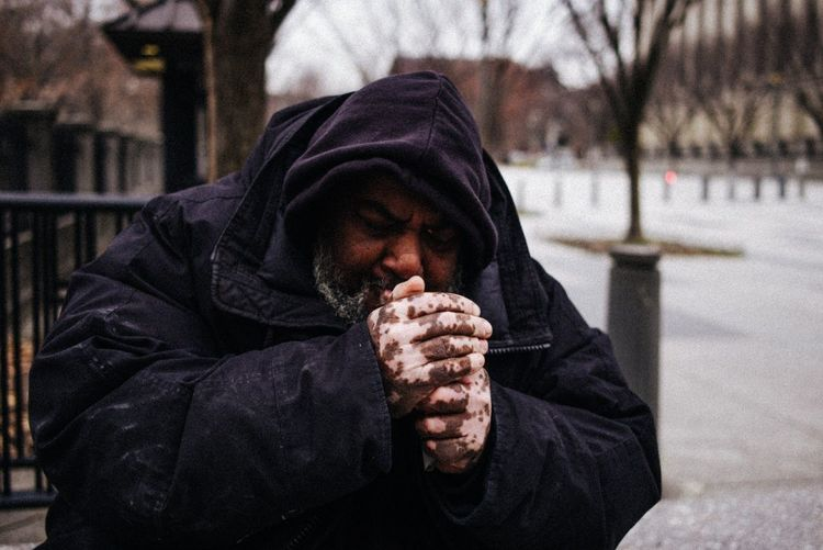 Man sitting on snow covered street