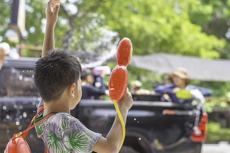 Rear view of boy holding squirt gun