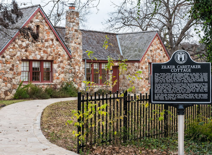 AUSTIN, TEXAS - DECEMBER 30, 2017: Built in the 1930's, the Zilker Caretaker Cottage housed many caretakers and their families. The cottage is now a museum for the public. Austin Texas Caretaker Architecture Building Building Exterior Built Structure Caretaker Cottage Day House Information Information Sign Museum Nature No People Outdoors Plant Public Rural Scene Sign Text Tree Zilker Park