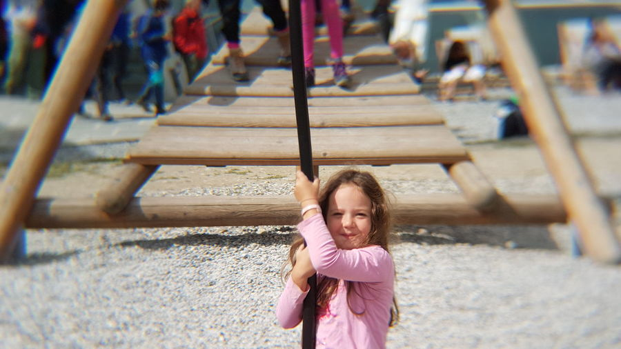 Portrait of girl hanging from rope in playground during sunny day