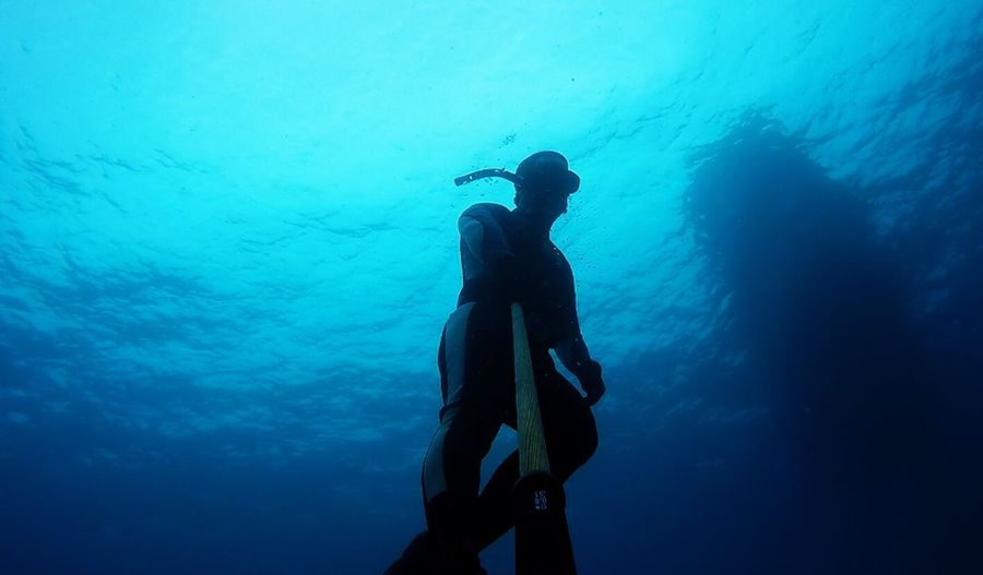 Low angle view of man taking selfie with monopod in sea