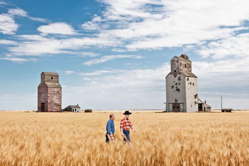Men standing on field against sky