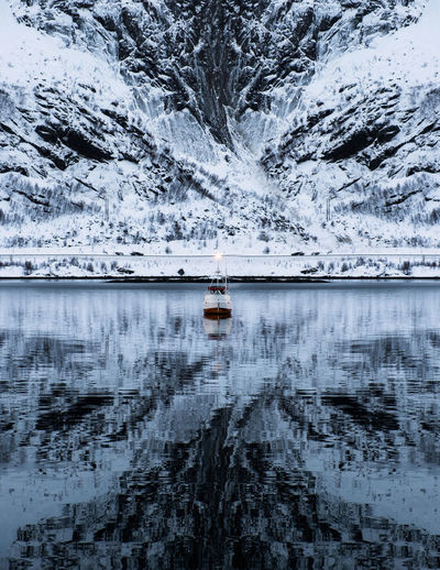 Scenic view of lake during winter against mountain