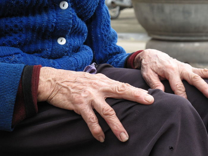 Midsection Of Senior Woman Sitting Outdoors