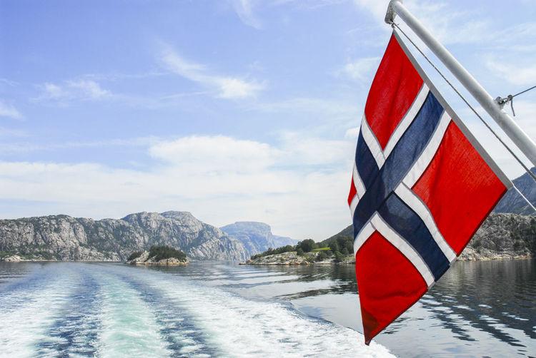 Norwegian flag over sea against sky