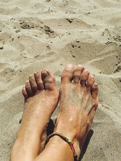 Close-up low section of legs on sand
