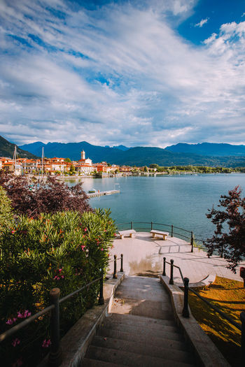 Feriolo village on lake maggiore with cloudy sky and steps to walk along the lake in the foreground