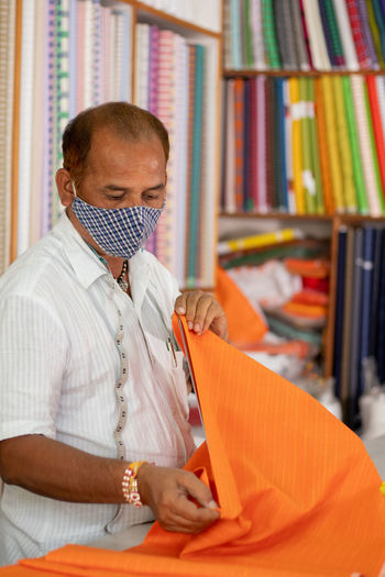 Tailor wearing protective face mask while working in shop