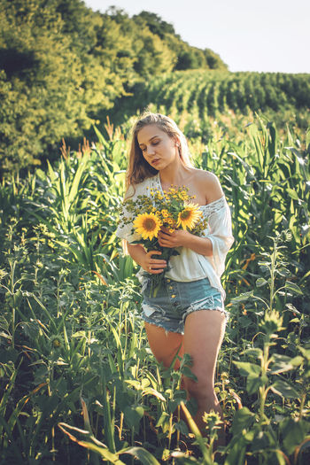 young woman holding bouquet standing in field