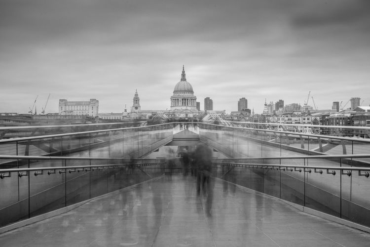 Blurred motion of people walking on london millennium footbridge against st paul cathedral