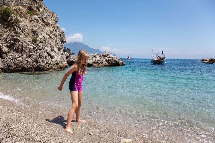 Girl on beach against sky
