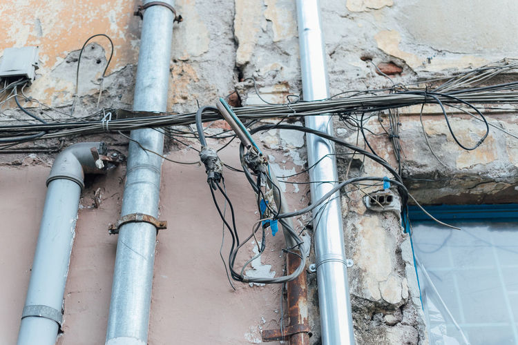 Pipe - Tube No People Architecture Metal Built Structure Cable Fuel And Power Generation Connection Day Electricity  Wall - Building Feature Pipeline Building Exterior Pipe Technology Power Supply Wire Power Line  Outdoors Low Angle View How Now Brown Cow Catastrophe Unprofessional Not Professional Provisionally