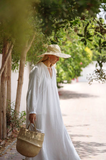 Woman wearing white dress walking in the garden barefoot