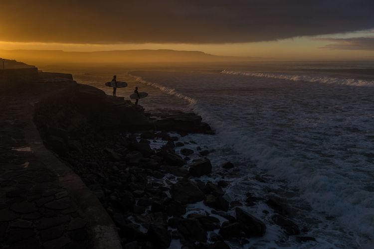 Surfers looking at sea at dusk