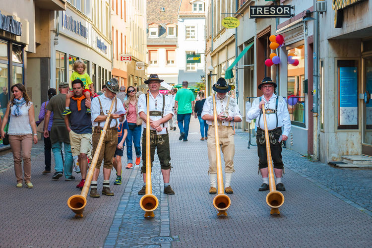 Alphorn player in traditional Bavarian costumes performing on the street of the Heidelberg's old town at the fall folk festival. Alphorn Oktoberfest Adult Alphorn Player Alpine Horn Architecture Bavarian Clothes Bavarian Clothing Building Exterior City Crowd Festival Front View Full Length Group Of People Labrophone Musician People Perform Real People Standing Street Uniform Wooden Young Adult #urbanana: The Urban Playground EyeEmNewHere