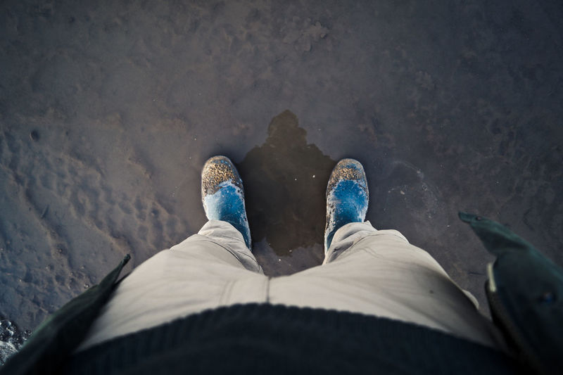 Low section of person standing on wet road