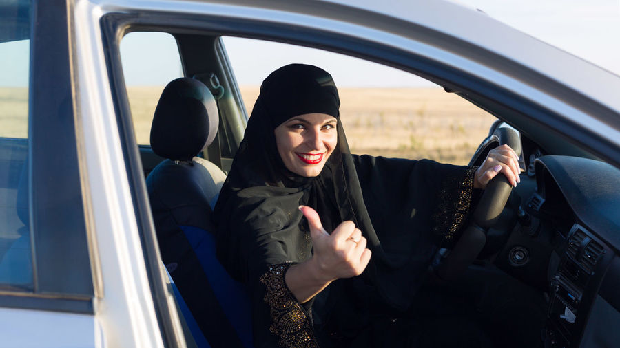 Portrait of woman wearing hijab showing thumbs up in car
