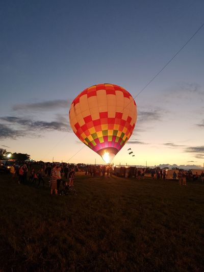 People and hot air balloon against sky during sunset