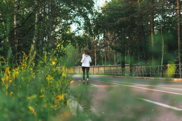 Young slim woman brunette in sport clothes running at autumn park on sunrise time
